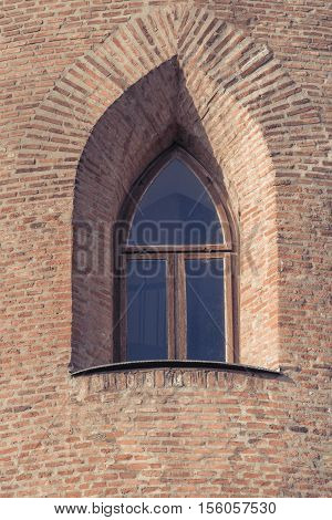 Window in old citadel. Old window in the wall of a medieval building in Europe. Window in old brick wall ruins of a medieval fortress. Old arched without glass window in a brick wall.