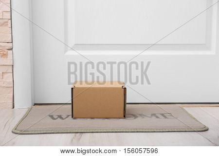 Cardboard box on rug under entrance door