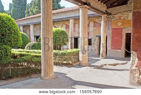 The antique villas had the inner gardens surrounded by shady painted galleries with columns Pompeii Italy.
