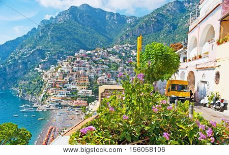 The with old colorful villas of Positano and the comfortable sand beach are seen behind the bright flower shrub Positano Italy.