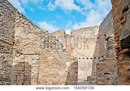 The preserved stone walls of the ancient Roman villa on territory of Pompeii archaeological site Italy.
