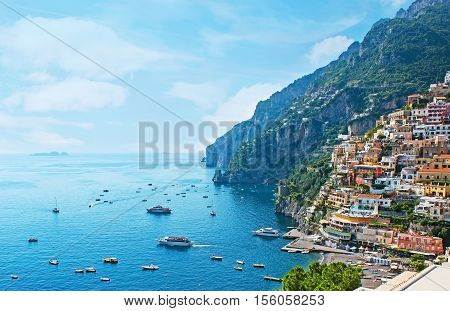 One of the best resorts of Italy with old colorful villas on the steep nice beach numerous yachts and boats in harbor and medieval towers along the coast Positano.