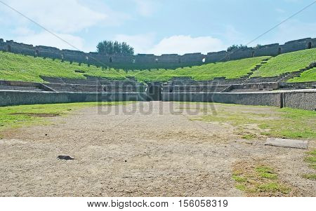 The walk along arena of the ancient Amphitheater of Pompeii Italy.