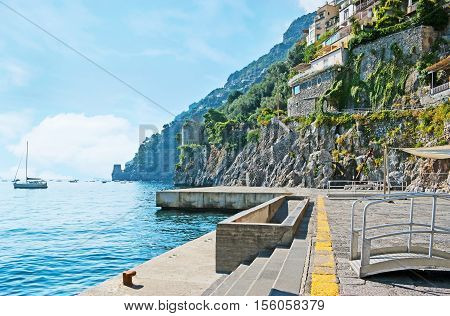 The sea promenade of Positano is the best place to discover the indented coast huge rocks old villas on the slopes ruins of the medieval watch towers yachts and fishing boats in harbor Italy.