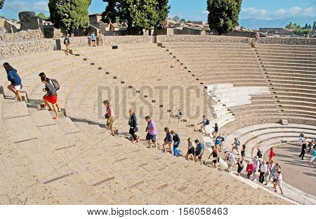 POMPEII ITALY - OCTOBER 4 2012: The tourists go up the stairs to the top of Grand Theater on October 4 in Pompeii.