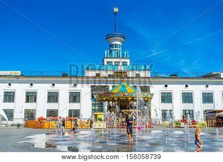 KIEV UKRAINE - SEPTEMBER 8 2016: Children play in fountain in Postal (Poshtova) Square with the River Port on the background on September 8 in Kiev.