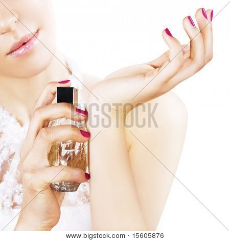 Woman spraying perfume on her wrist. Focus on hands and perfume bottle.