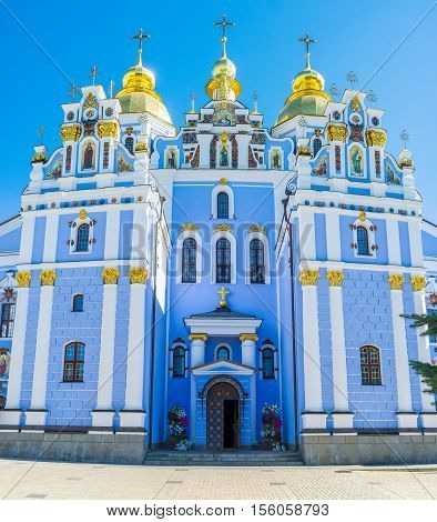 The bright blue facade of Cathedral of St Michael's Golden-Domed Monastery decorated with fretwork colorful traceries icons and shining golden onion domes Kiev Ukraine.