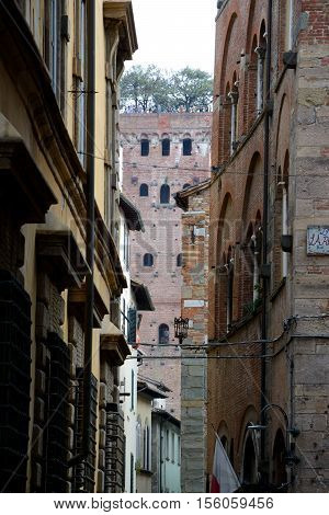 Lucca Italy - September 5 2016: Buildings and Guinigi tower in old part of Lucca city in Italy. Unidentified people visible.
