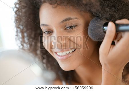 Beautiful mixed-race woman putting makeup on
