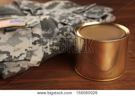 Uniform of American soldier and combat ration on wooden background, close up view
