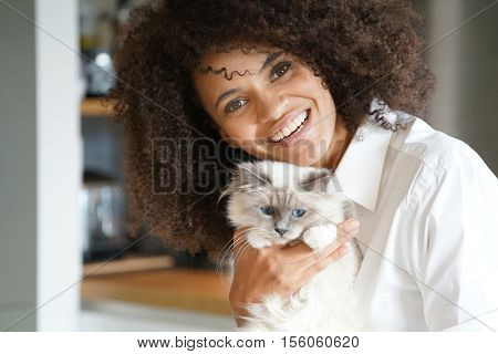Portrait of mixed race woman cuddling cat