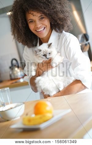 Mixed-race woman in kitchen cuddling cat
