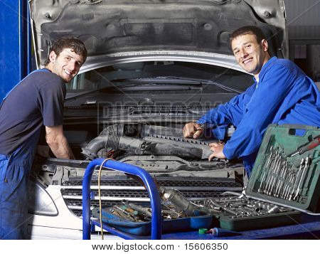 Auto mechanics near car. Different working tools on foreground