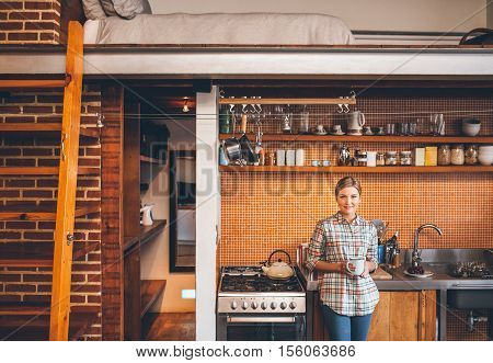Portrait of an attractive young blonde woman drinking a cup of coffee while leaning against the counter in the kitchen of her modern loft apartment