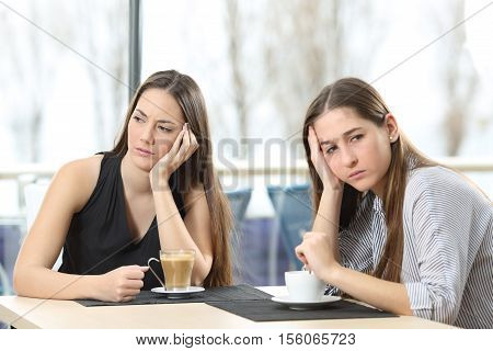 Two angry friends ignoring each other after argument in a coffee shop