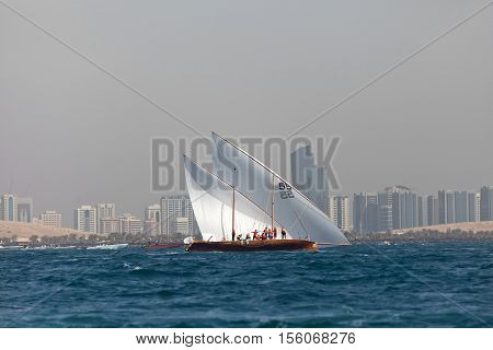 ABU DHABI, UAE - JUNE 7, 2014: Traditional sailing dhows race back to Abu Dhabi at Ghanada Dhow Sailing Race 60 ft. Final Round