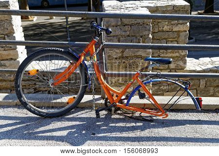bicycle abandoned on the street dismounted one wheel