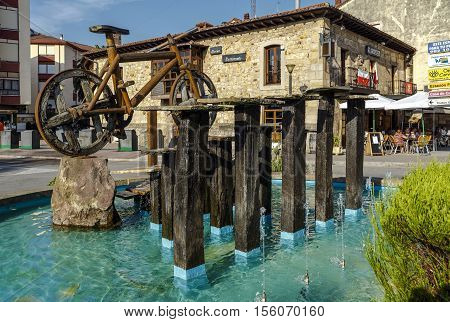 Cabezon De La Sal Spain - August 24 2016: Bicycle roundabout in the Plaza de la Paz in the Cantabrian town a monument made in wood with wheels of carriage. Decorate the roundabout also a fountain and various aromatic plants such as rosemary and lavender.