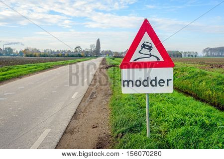 Traffic sign indicating mud in an agrarian landscape in the Netherlands. It's autumn and harvest time for sugar beets and a lot of mud is on the rural roads.