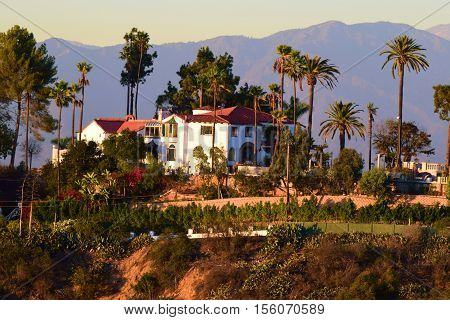 Spanish style Villa Mansion on top of a hill with amazing views surrounded by Palm Trees with mountains beyond taken in the Los Angeles, CA area