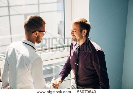 Full length side view of businessmen shaking hands in modern office building on stairs
