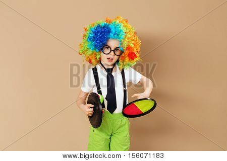 Kid In Clown Wig And Eyeglasses Playing Catch Ball Game