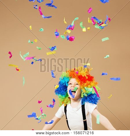 Little Boy In Clown Wig Jumping And Having Fun Celebrating Birthday. Portrait Of A Child Throws Up A