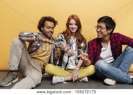 Three happy young people sitting and playing rock paper scissors game over yellow background