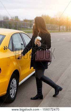 Brunette with long hair, opensing door of yellow taxi in afternoon in city