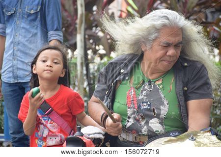 KUALA LUMPUR, MALAYSIA - DECEMBER 31, 2015 - Unidentified malaysian man with white long hairs playing music on the street with his niece