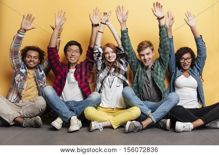 Multiethnic group of happy young people sitting together with raised hands over yellow background