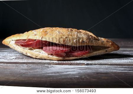 Tasty satiety sandwich with panini and sausage and butter on the wooden table