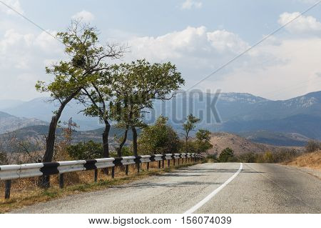 Russian .Crimea. Sudak. Wide road with fence on background of mountain scenery. 14.09.2016