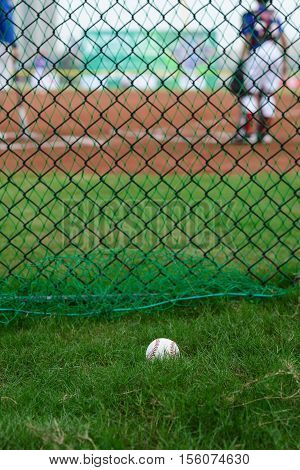 baseball outside of a baseball field with batter and catcher at background selective focus