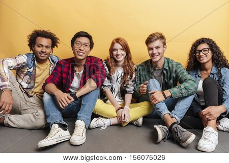 Multiethnic group of smiling young friends sitting on the floor together over yellow background