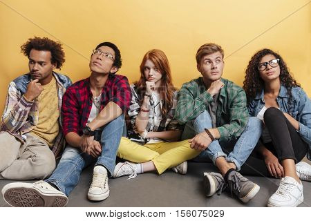 Multiethnic group of thoughtful young friends sitting and thinking over yellow background