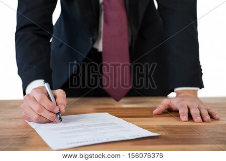 Mid-section of businessman filling last will and testament form against white background