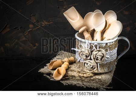 Wooden spoon and scoop in the aluminum mug with handmade decor of burlap and lace. Mug is on a napkin of burlap on dark textured background. Tinted photo