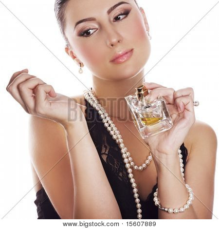 Woman in classic style applying perfume on her wrest. Focus on face.