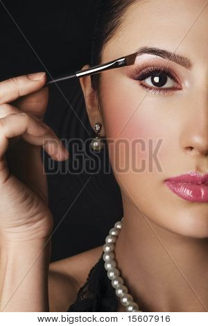 Elegant woman applying makeup on her eye