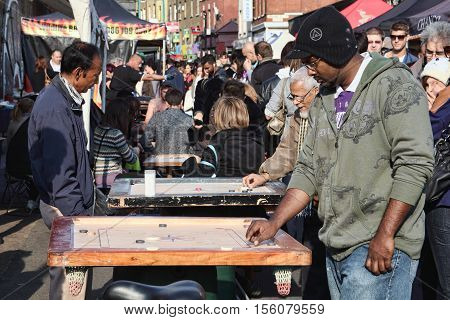 London, UK - October 23, 2011:  Customers playing a Corrom table game at a market stall in Brick Lane street flee market