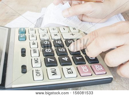 finger to press calculator checking document and slip monthly expenses credit card accounting