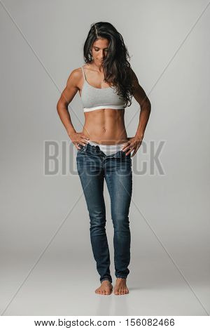 Single pretty woman wearing unzipped tight blue jeans with hands on hips while looking at her bare feet over neutral gray background