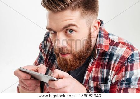 Close up portrait of a suspicious bearded man in plaid shirt playing game on his smart phone over white background