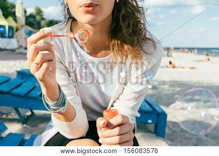 Girl In The Skirt And Cardigan Blow Bubbles On The Beach