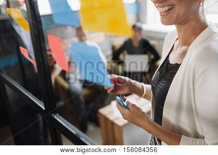 Smiling young woman brainstorming using adhesive notes on glass wall. Presenting ideas to colleagues during meeting.