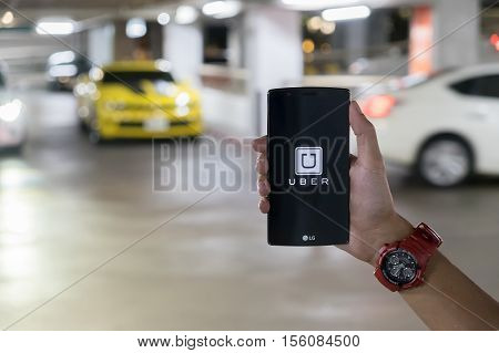 CHIANG MAITHAILAND - AUG 23 2016 : A man hand holding Uber app showing on LG G4 on road and red car Uber is smartphone app-based transportation network.