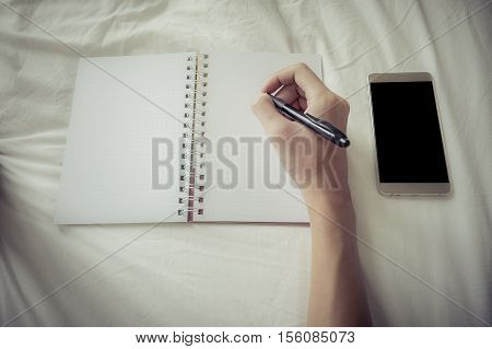 Business Man Laydown On Bed And Hand Holding Pen For Working In Bedroom With Smartphone Blank Screen