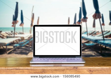 laptop blank screen on wooden desk with beach and sea and umbrella in the summer sun blur background.relax concept. Front view.